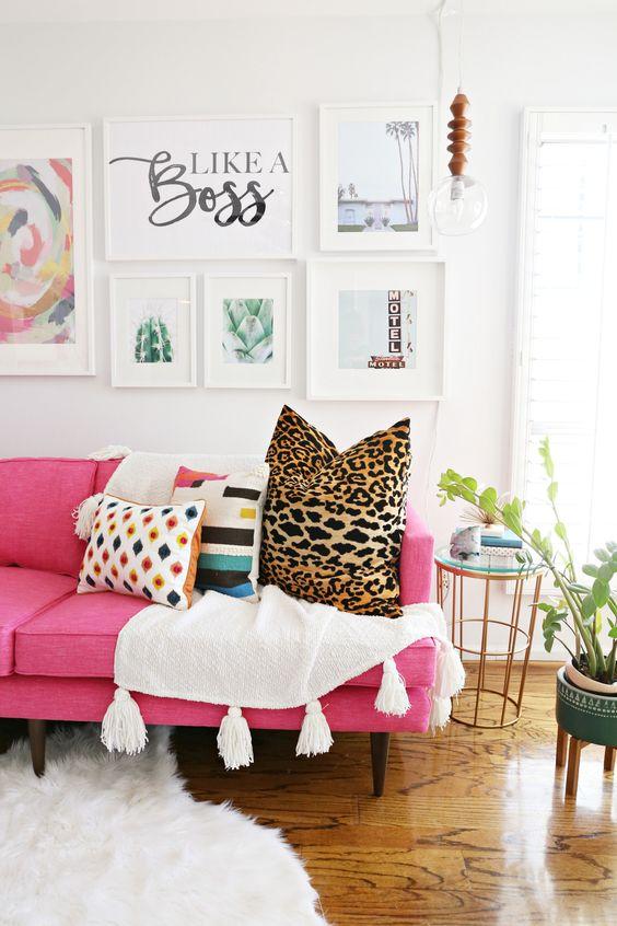 un soggiorno moderno con un divano rosa caldo, cuscini stampati, un'elegante galleria a parete, una lampadina a sospensione e piante in vaso
