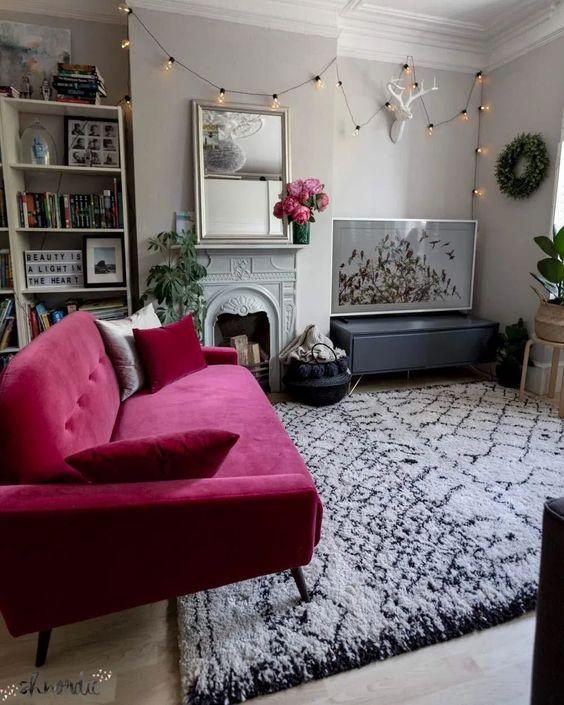 un delizioso soggiorno neutro contemporaneo con scaffali incorporati, un camino non funzionante, un divanetto rosa caldo, piante in vaso e una bella parete della galleria