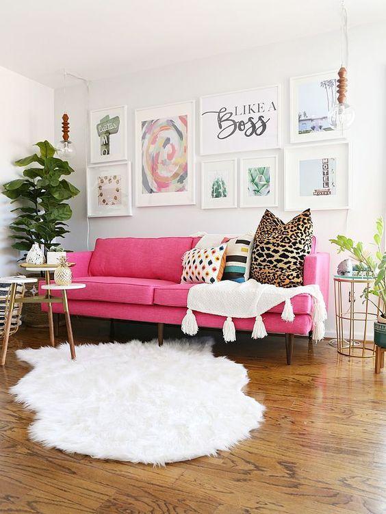un bel soggiorno moderno fatto in colori neutri, con un divano rosa, un arioso muro della galleria, tessuti bianchi, piante in vaso e alcuni tavoli