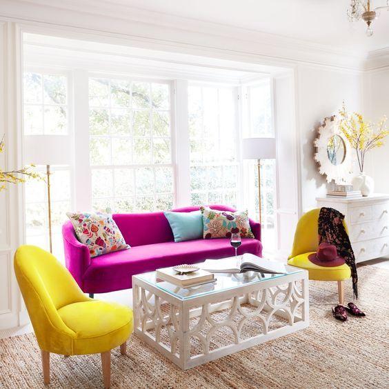 un elegante soggiorno neutro in moderno stile rustico, con un divano rosa caldo, sedie giallo sole, un tavolo di vetro e cuscini colorati