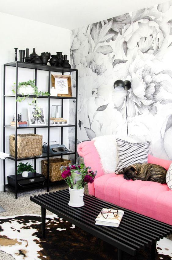 un grazioso soggiorno monocromatico con una parete floreale, un mobile contenitore, un tavolo nero e un divano rosa brillante con cuscini stampati