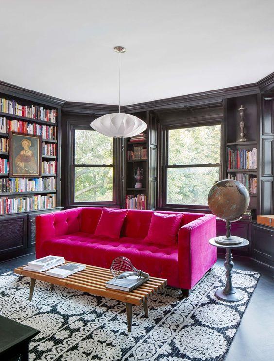una stanza lunatica con una finestra a bovindo, librerie incorporate, un divano trapuntato rosa caldo per un accento di colore nello spazio