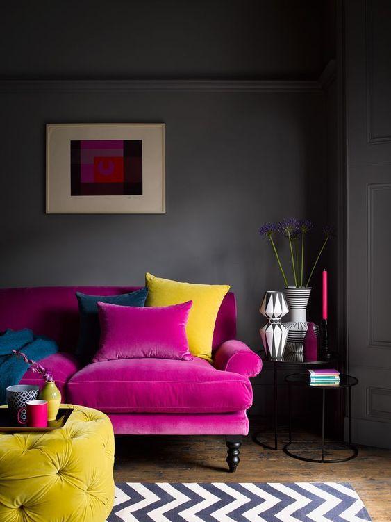 un soggiorno lunatico con pareti grigie, un divano rosa caldo, un ottomano trapuntato giallo, un tappeto stampato, vasi e candele chic