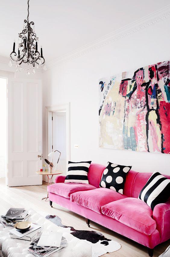 un raffinato soggiorno contemporaneo con un divano rosa caldo con cuscini stampati, un'opera d'arte audace, un lampadario di cristallo e un ottomano bianco