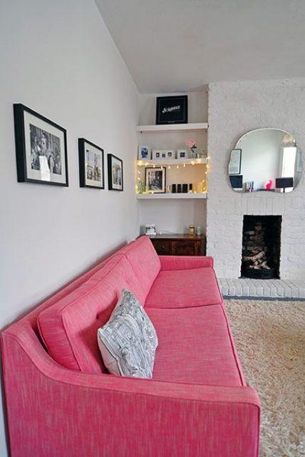 un soggiorno neutro con un camino non funzionante, mensole incorporate, un divano rosa per un tocco di colore audace e una parete a griglia