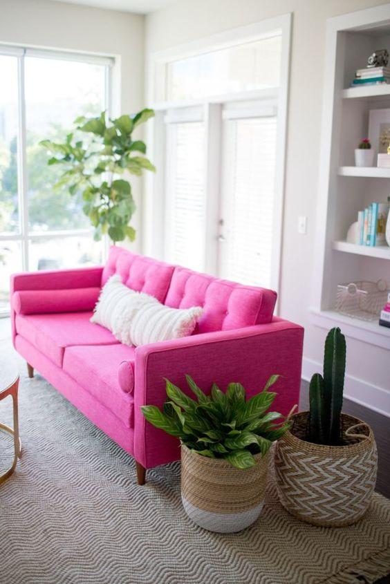 uno spazio neutro decorato con un divano rosa caldo, un tappeto boho e cuscini, piante in vaso in cesti è una stanza fresca