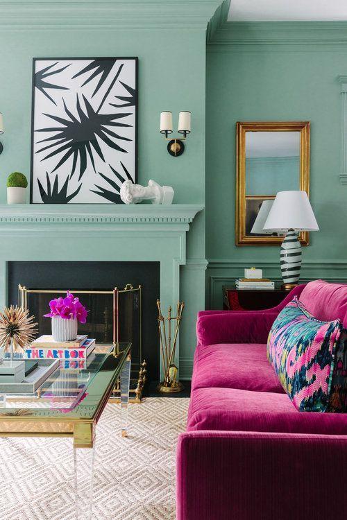 un soggiorno verde pastello con un camino non funzionante, belle opere d'arte, un divano fucsia con cuscini florla e un bel tavolo