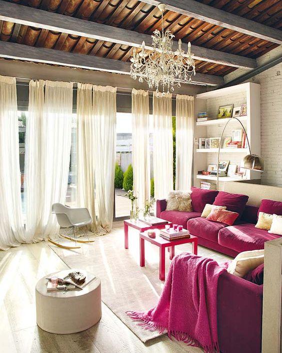 un raffinato soggiorno neutro con mensole incorporate, due divani fucsia, mobili e tessuti neutri più un lampadario di cristallo