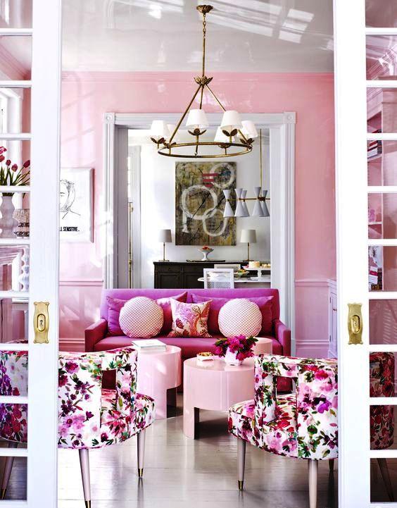 un raffinato soggiorno femminile con pareti rosa, un divanetto rosa, sedie floreali, tavolini e cuscini arrossati e un lampadario chic