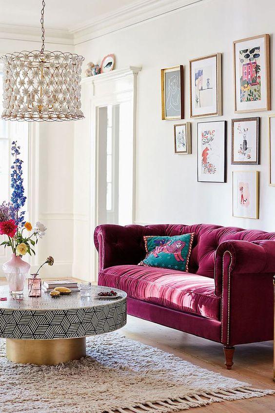 un raffinato soggiorno con un divano capitonné rosa, una galleria a parete, un tavolo geometrico e dorato, un lampadario floreale è wow