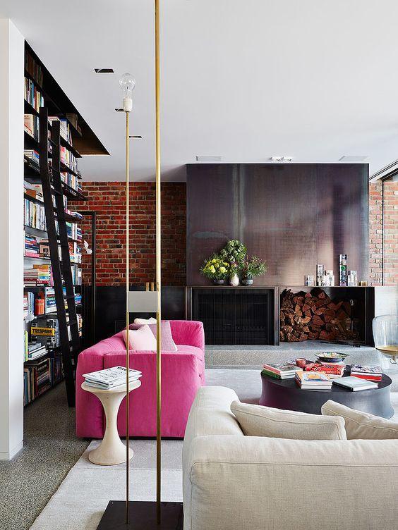 un elegante soggiorno contemporaneo con camino in metallo e legnaia, un divano rosa caldo, uno neutro, una grande libreria e tocchi d'oro