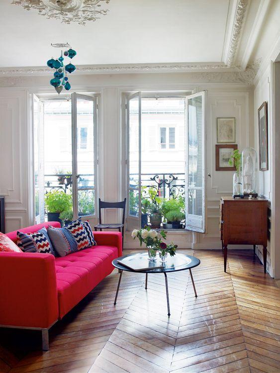 un elegante soggiorno con un divano capitonné rosa caldo, un tavolo basso, una credenza in legno e molte piante in vaso sul balcone