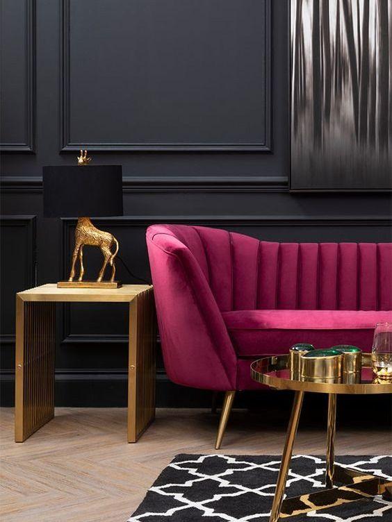 uno spazio raffinato e lunatico con pareti rivestite di pannelli neri, un divano fucsia, un lato dorato e un tavolino da caffè, una lampada da tavolo creativa e un tappeto stampato