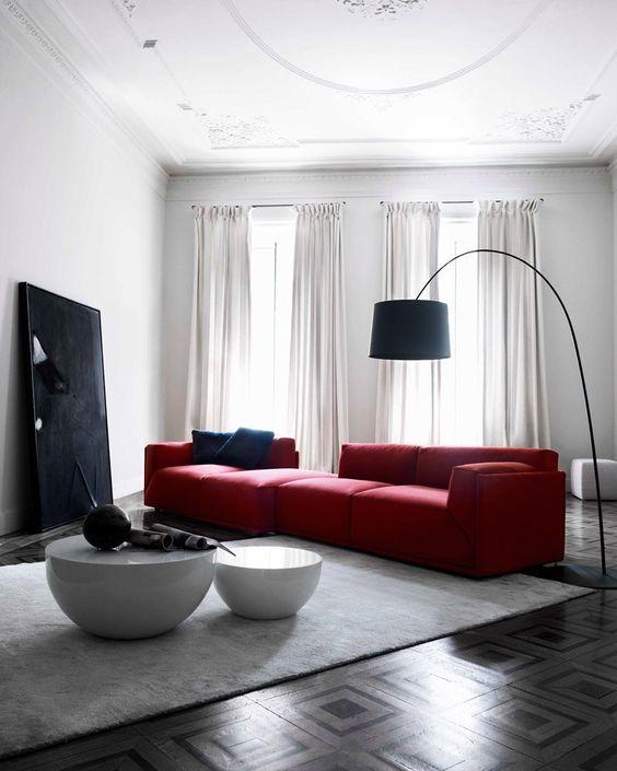 un audace soggiorno contemporaneo con un grande divano rosso, un'opera d'arte nera e una lampada da terra e un duo di tavoli rotondi
