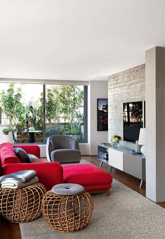 un elegante soggiorno moderno con un muro di cemento, una credenza bicolore, un audace componibile rosso, una sedia grigia e pouf in rattan