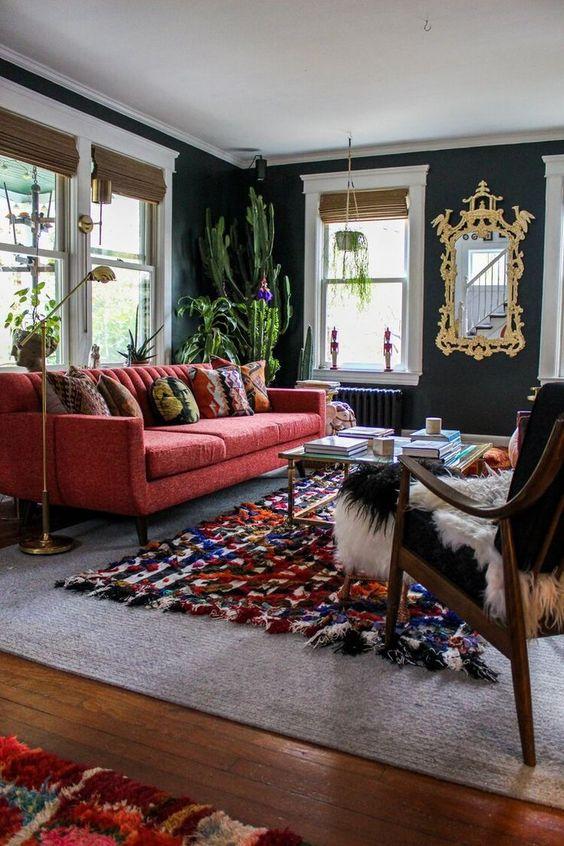 un soggiorno moderno chic con pareti grigio grafite, un divano rosso, un tappeto colorato, una sedia nera e cactus in vaso è wow