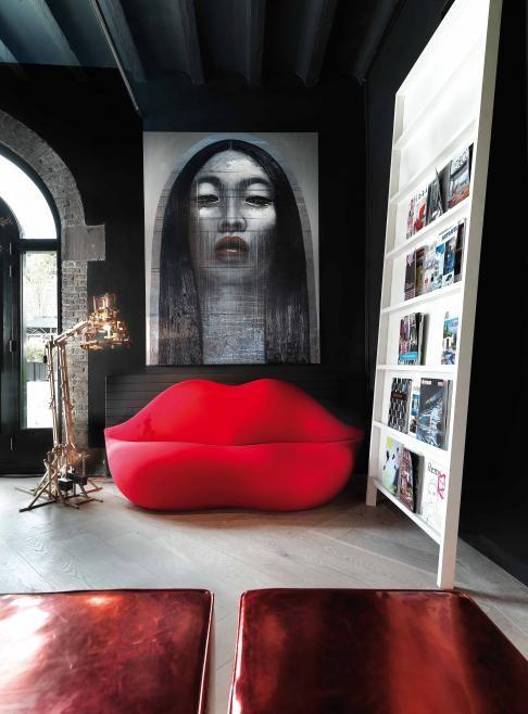 un soggiorno accattivante con pareti scure, un mobile contenitore con sporgenza creativa e un divano a forma di labbro ared e un'opera d'arte audace