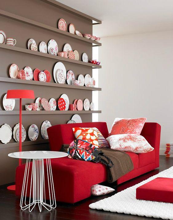 un angolo chic con una parete color talpa e una collezione di piatti decorativi, un divano rosso e cuscini stampati più un tavolo rotondo