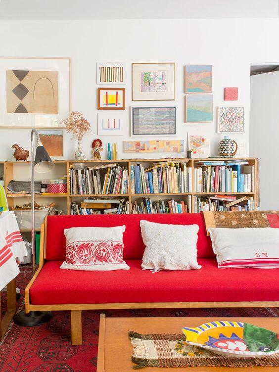 un luminoso soggiorno eclettico con un audace divano rosso, librerie, una luminosa galleria a parete e un tavolino basso