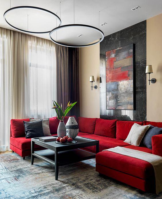 un elegante soggiorno contemporaneo con un componibile rosso, un'opera d'arte audace, lampade a sospensione, un tavolino nero e vari cuscini