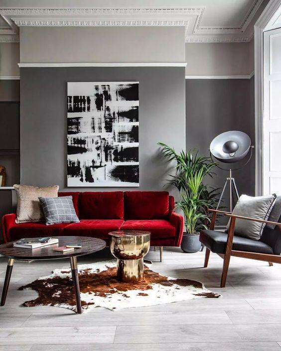 un soggiorno moderno con pareti grigie, un divano rosso audace, una sedia in pelle nera, un'opera d'arte monocromatica e un tavolo rotondo