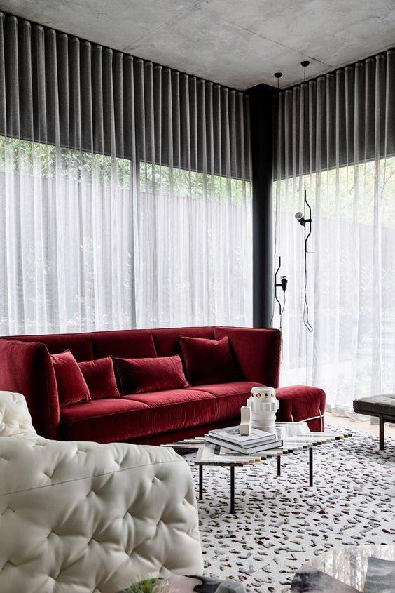 un fresco spazio monocromatico con mobili in bianco e nero, un tappeto stampato e materico e un audace divano rosso per un tocco di colore