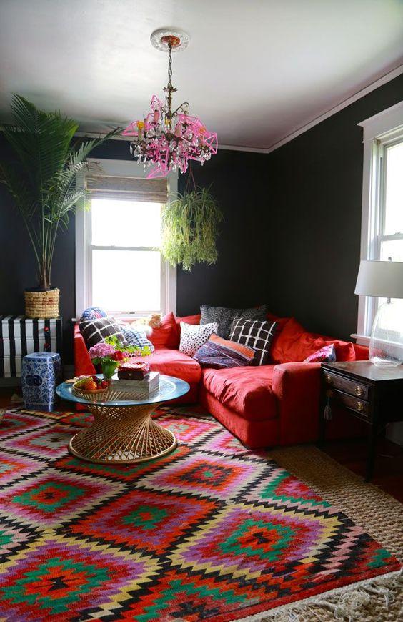 un soggiorno colorato con pareti nere, un divano rosso, un tappeto audace, un lampadario rosa e alcune piante in vaso è fantastico