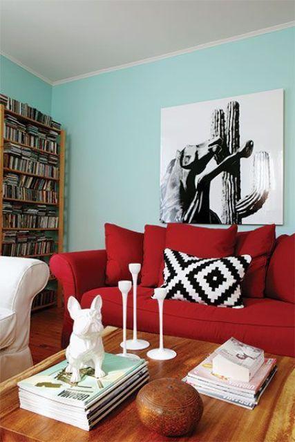un soggiorno moderno con pareti turchesi, un divano rosso audace, una libreria, un'opera d'arte monocromatica e un tavolo basso con decorazioni