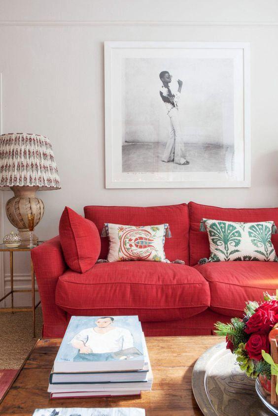 un soggiorno moderno con un audace divano rosso, cuscini stampati, un'opera d'arte, una lampada stampata e pile di libri