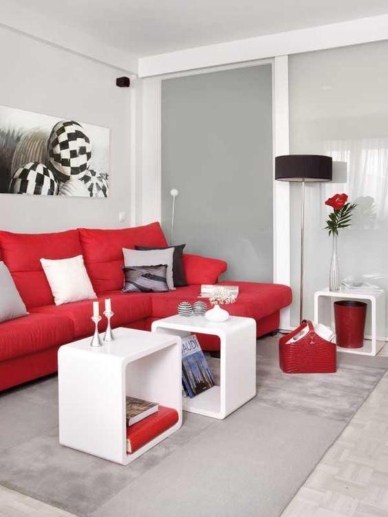 un soggiorno contemporaneo monocromatico in bianco e grigio chiaro, con un audace divano rosso e altri tocchi per un look più luminoso
