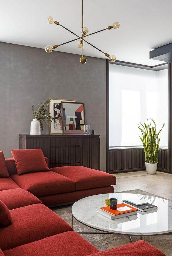 un laconico soggiorno moderno con pareti grigie, un componibile rosso scuro, un mobile contenitore in legno e un tavolo rotondo basso