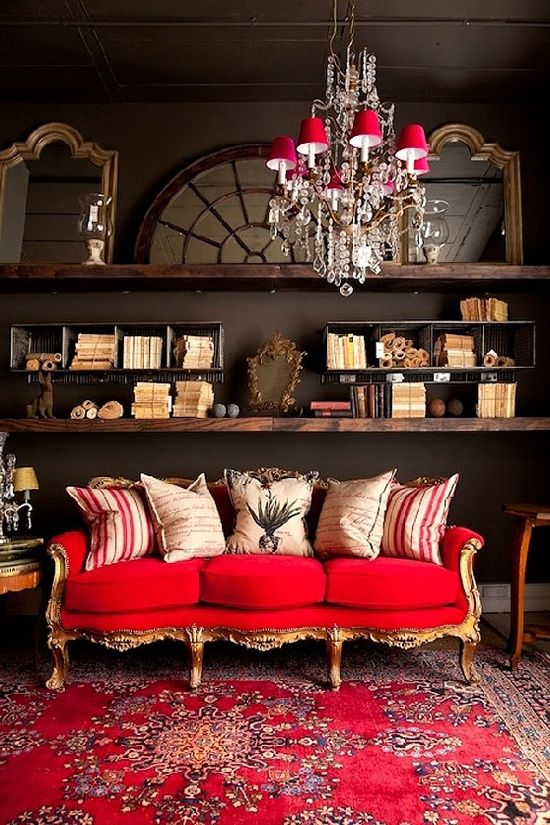 un raffinato soggiorno eclettico con pareti scure, scaffali macchiati di scuro, un raffinato divano rosso e oro e un lampadario accattivante