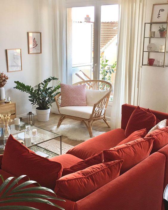 un soggiorno neutro con mobili in rattan e legno, un divano rosso con cuscini, piante in vaso e un mobile contenitore sul muro