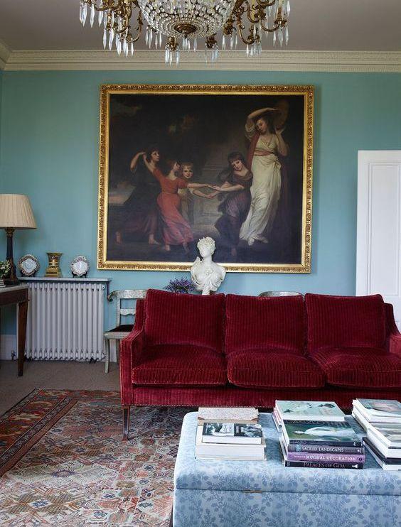 un raffinato soggiorno con pareti blu, un divano rosso intenso, un ottomano floreale, un'audace opera d'arte vintage e un lampadario di cristallo