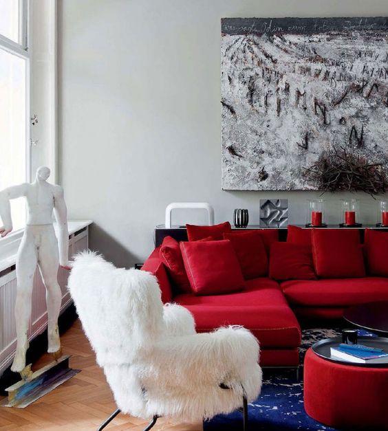 un raffinato soggiorno moderno con un componibile rosso caldo, una sedia in pelliccia sintetica bianca, un pouf rosso audace e un'opera d'arte creativa