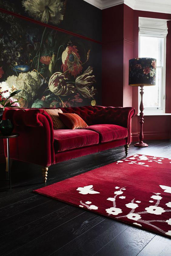 un soggiorno lunatico e raffinato con un murale floreale audace, un divano rosso intenso, un tappeto floreale, lampade floreali e pareti bordeaux