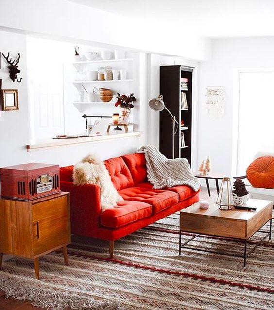 un grazioso soggiorno moderno della metà del secolo realizzato in colori neutri e arricchito con tocchi audaci: un divano rosso, una cassa e un cuscino arancione