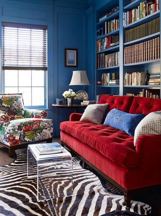uno spazio vivace con pareti blu, librerie incorporate, un divano rosso e una sedia floreale, tappeti a strati e un tavolo in acrilico