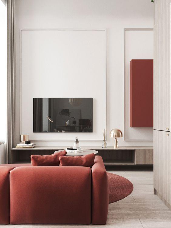 un elegante soggiorno contemporaneo fatto in neutri, con pareti bianche, mobili tinti di luce, un divano rosso e un tappeto è bello