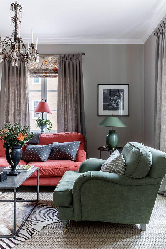 un interno d'ispirazione scandinava vintage con pareti grigie, un divano rosso, una sedia verde e un lampadario di cristallo vintage