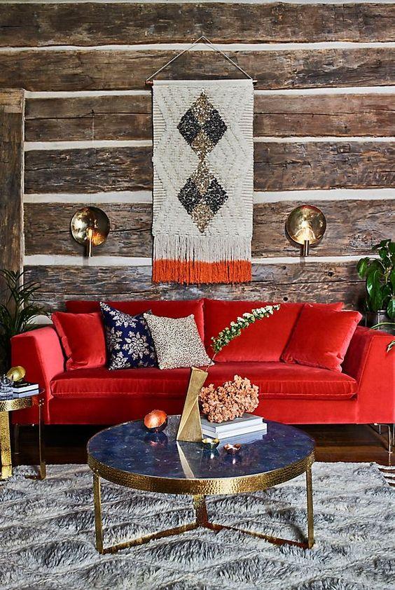 un soggiorno rustico con pareti in carta da parati in legno, un divano rosso audace, un raffinato tavolo in marmo blu e tocchi d'oro qua e là