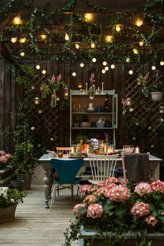 uno spazio da pranzo nel terrazza con luci a corda sullo spazio e lanterne a candela sul tavolo più fiori intorno