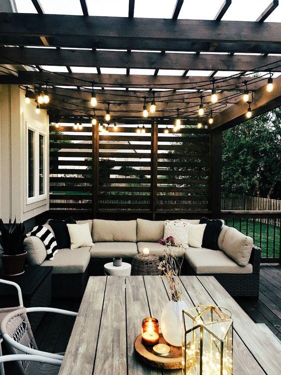 un terrazza moderno con mobili eleganti, luci a corda sullo spazio e alcune candele e luci direttamente sul tavolo