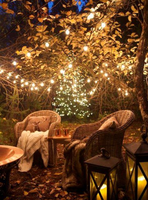 un accogliente giardino con sedie in rattan, molte luci sugli alberi e lanterne a candela e un pozzo del fuoco è molto invitante