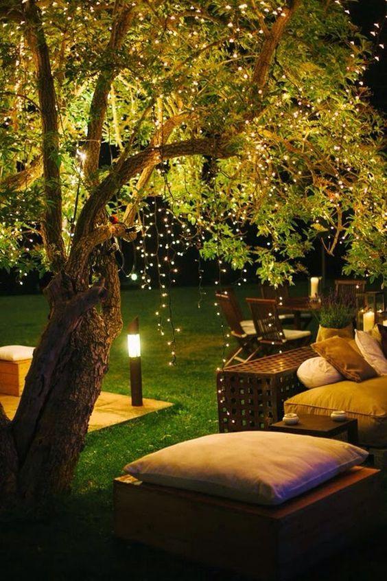 uno spazio giardino contemporaneo con mobili comodi e luci a corda sospese sopra lo spazio e lampade da esterno