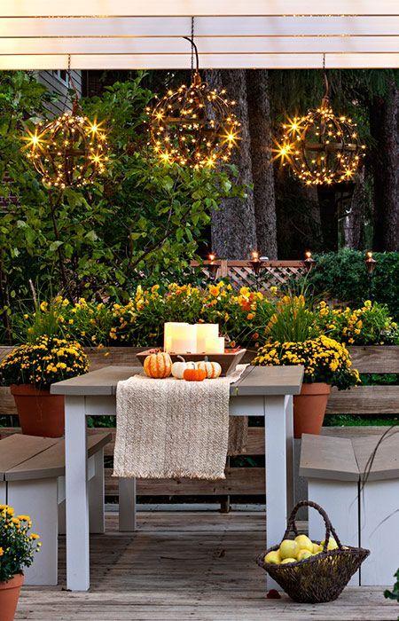 un luminoso mazzo autunnale con mobili eleganti e semplici, fiori in vaso, candele in una ciotola per un centrotavola e sfere luminose sul tavolo