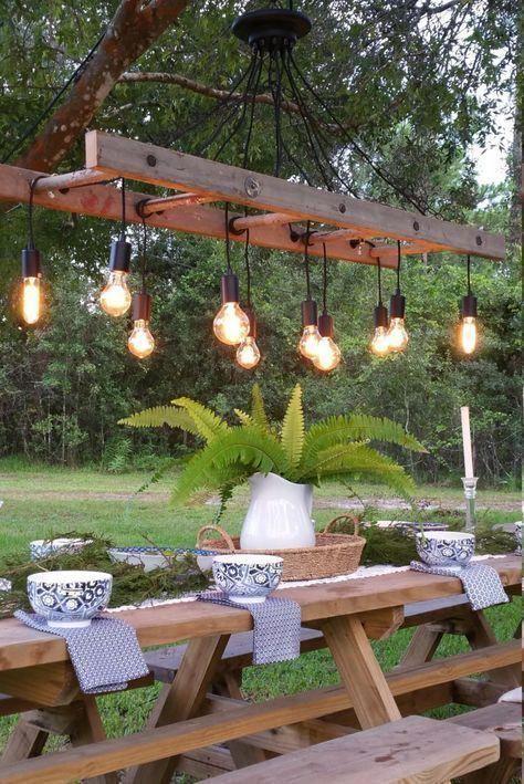 un eccentrico spazio da pranzo all'aperto con semplici mobili in legno e un accattivante lampadario a scala con lampadine è wow
