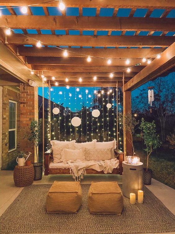 le normali luci a corda verticali e le lampade di carta e le candele e un pozzo del fuoco moderno sono un'idea elegante per un terrazza