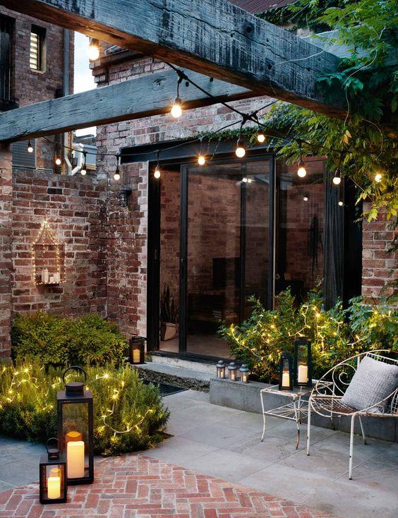 un cortile raffinato con lucine sulle piante, luci a filo nello spazio e lanterne a candela tutt'intorno