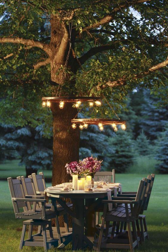 una zona pranzo all'aperto con mobili rustici in legno, candele sul tavolo e lampadari rustici a bulbo è incredibile